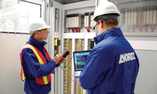 ANDRITZ employees configuring an electrical cabinet at an industrial site